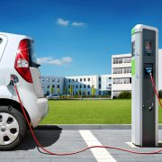 Elektroauto an Stromtankstelle vor Brogebude Elektromobilitt
