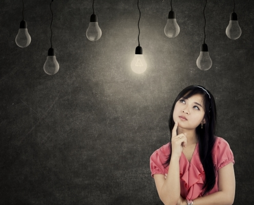 Thoughtful young businesswoman thinking idea while looking up with light bulbs